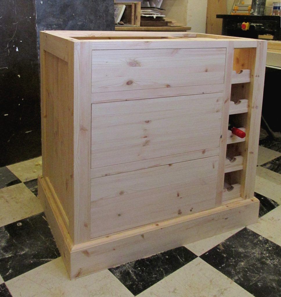 a kitchen island in unpainted pine with drawers and a wine rack