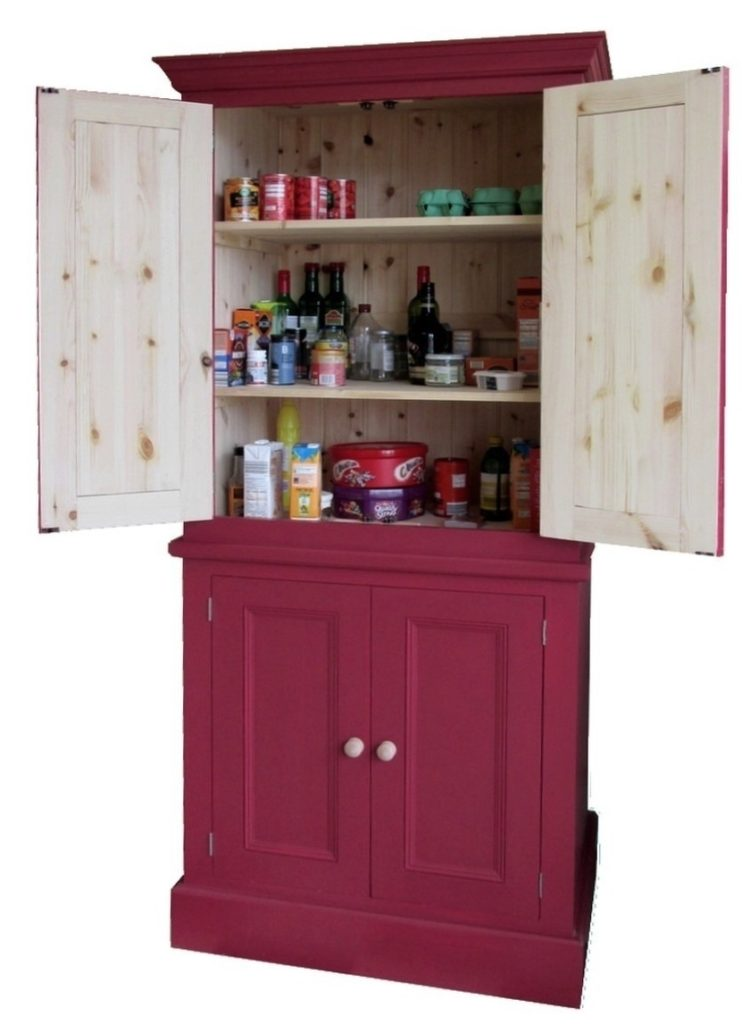 a red painted pine kitchen larder unit with the doors open and spice racks