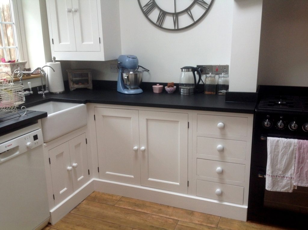 a painted solid wood kitchen painted white with a belfast sink
